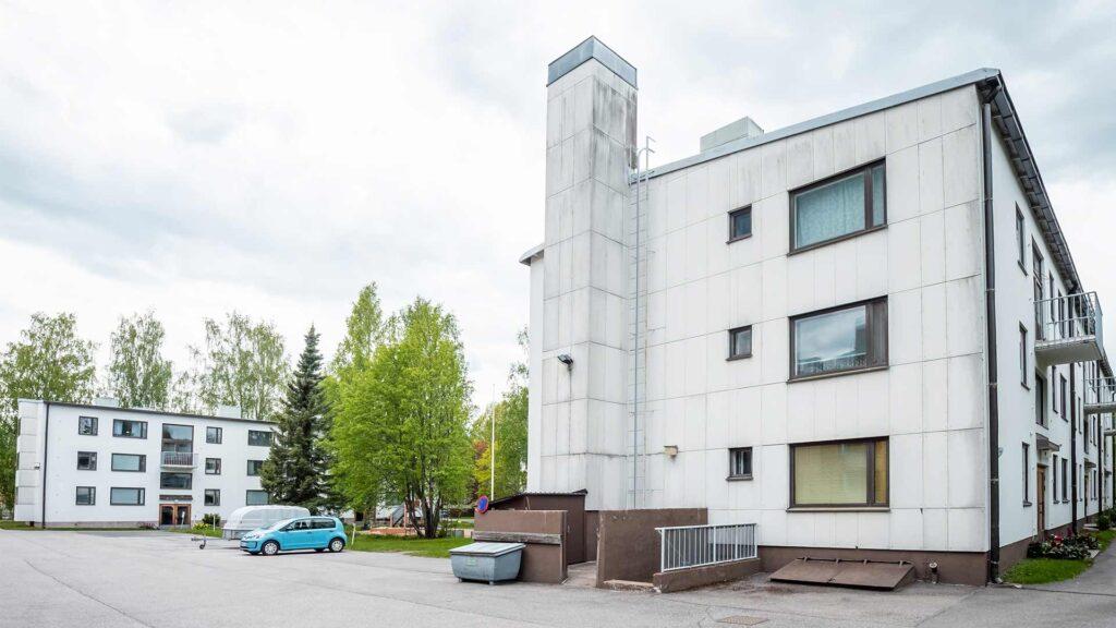 kuvassa valkoinen kolmikerroksinen kerrostalo kuvattuna pihalta, kuvassa mysö parkkialuetta ja autoja
